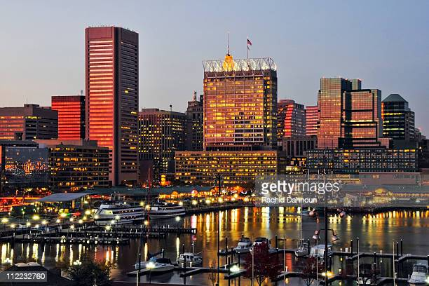 The sunset reflects off the windows of the Baltimore city skyline at dusk, Maryland.