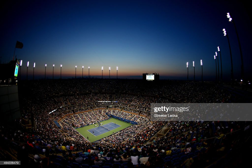 The sunsets as Roger Federer of Switzerland plays against Marinko Matosevic of Australia during their men's singles first round match on Day Two of the 2014 US Open at the USTA Billie Jean King National Tennis Center on August 26, 2014 in the Flushing neighborhood of the Queens borough of New York City.