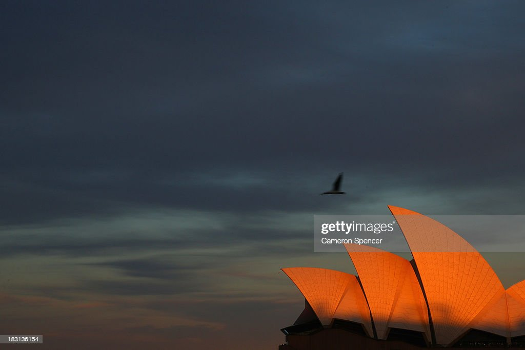 The sunsets on the Sydney Opera House during the International Fleet Review on October 5, 2013 in Sydney, Australia. Over 50 ships participate in the International Fleet Review at Sydney Harbour to commemorate the 100 year anniversary of the Royal Australian Navy's fleet arriving into Sydney. Prince Harry is an official guest of the Australian Government and will take part in the fleet review during his two-day visit to Australia.