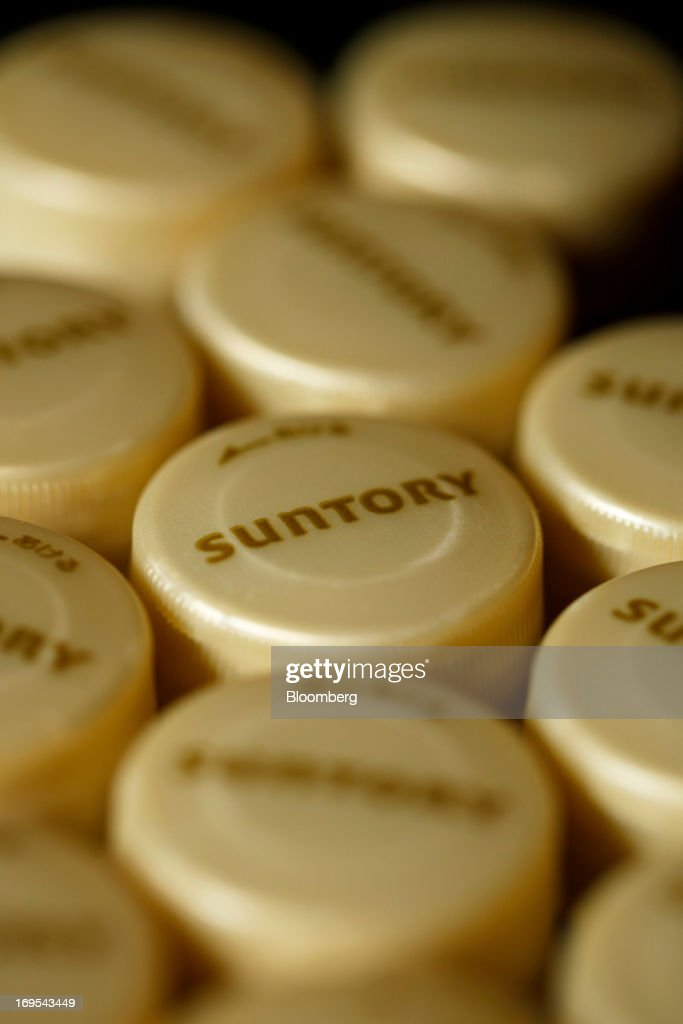 The Suntory Holdings Ltd. logo is displayed on bottle caps for Suntory Beverage & Food Ltd.'s Kuro Oolong tea are arranged for a photograph in Soka City, Saitama Prefecture, Japan, on Sunday, May 26, 2013. Nomura Holdings Inc., Morgan Stanley and JPMorgan Chase & Co. were selected as the lead banks to manage Suntory Beverage & Food Ltd.'s initial public offering, said two people with knowledge of the matter. Photographer: Kiyoshi Ota/Bloomberg via Getty Images