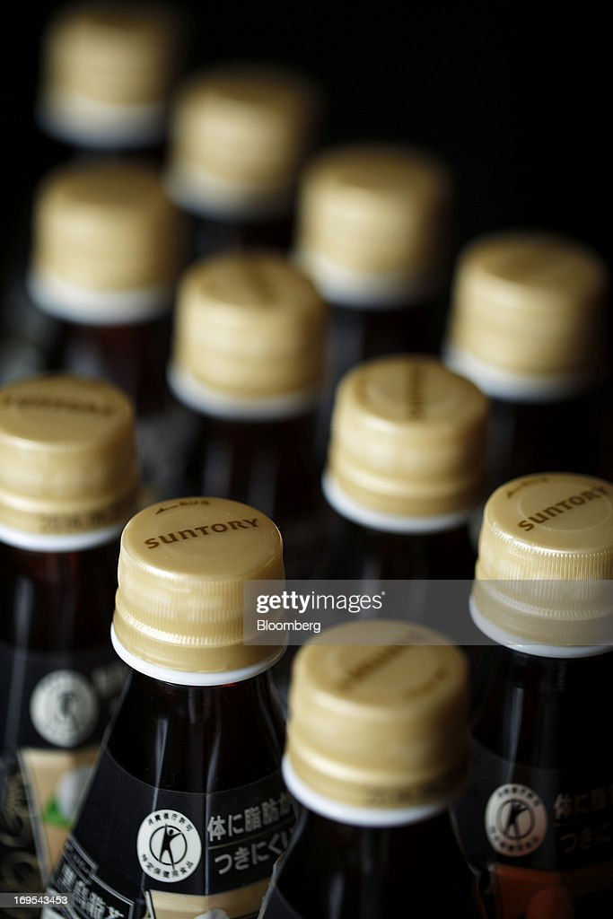The Suntory Holdings Ltd. logo is displayed on bottle caps for Suntory Beverage & Food Ltd.'s Kuro Oolong tea in this arranged photograph taken in Soka City, Saitama Prefecture, Japan, on Sunday, May 26, 2013. Nomura Holdings Inc., Morgan Stanley and JPMorgan Chase & Co. were selected as the lead banks to manage Suntory Beverage & Food Ltd.'s initial public offering, said two people with knowledge of the matter. Photographer: Kiyoshi Ota/Bloomberg via Getty Images