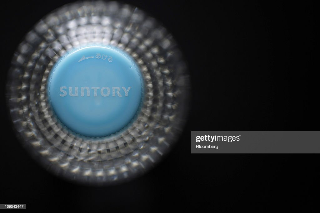 The Suntory Holdings Ltd. logo is displayed on the bottle cap for Suntory Beverage & Food Ltd.'s flavored water in this arranged photograph taken in Soka City, Saitama Prefecture, Japan, on Sunday, May 26, 2013. Nomura Holdings Inc., Morgan Stanley and JPMorgan Chase & Co. were selected as the lead banks to manage Suntory Beverage & Food Ltd.'s initial public offering, said two people with knowledge of the matter. Photographer: Kiyoshi Ota/Bloomberg via Getty Images