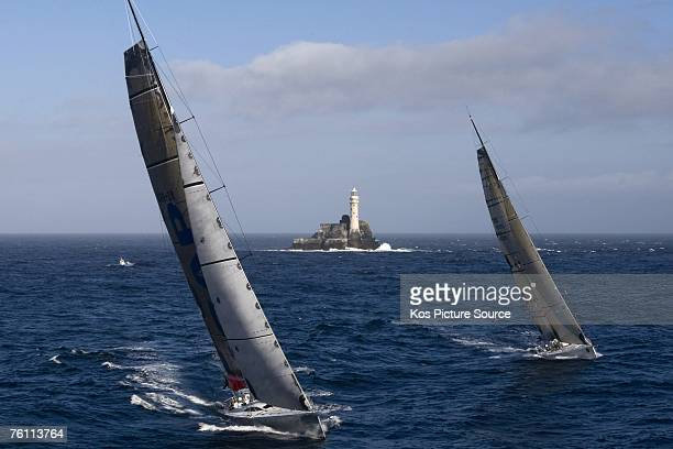 The super maxi yacht Rambler leads the canting keel maxi ICAP Leopard owned by Mike Slade around the Fastnet Lighthouse by a mere 3 seconds during...