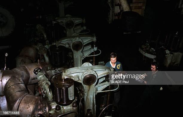 The Super Tanker Tarfala En mer dans la salle des machines du supertanker deux hommes en bleu de travail avec un casque sur les oreilles l'un tenant...