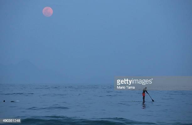 The supermoon rises above a man riding a standup paddle board off Copacabana Beach on September 27 2015 in Rio de Janeiro Brazil Tonight's supermoon...