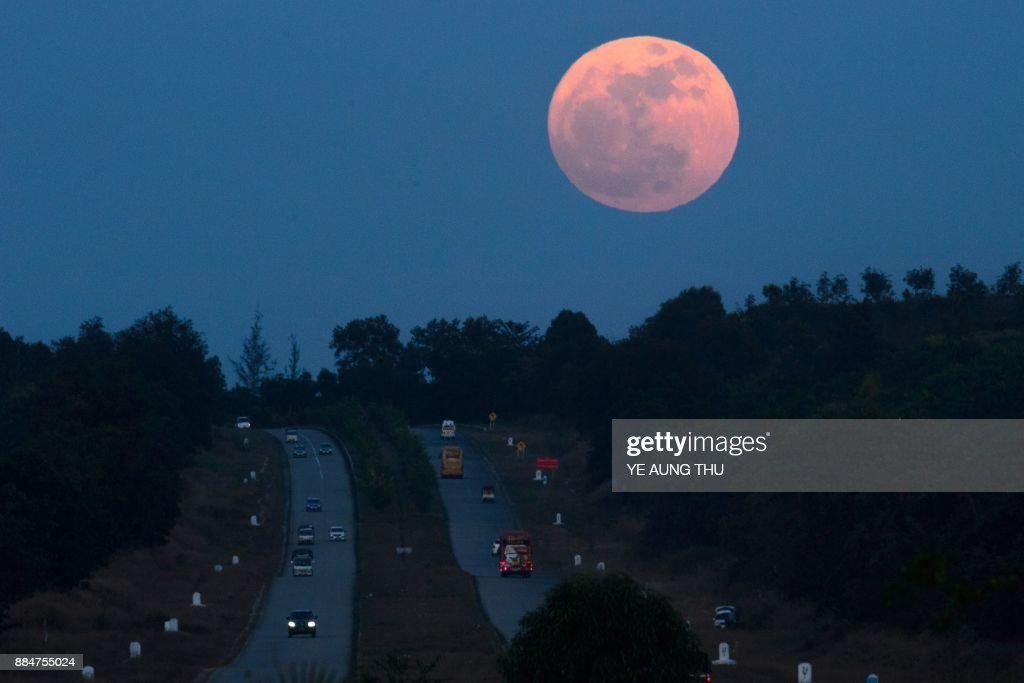 TOPSHOT - The supermoon rises over a highway near Yangon on December 3, 2017. The lunar phenomenon occurs when a full moon is at its closest point to earth. / AFP PHOTO / Ye Aung THU