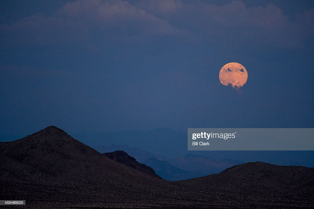 The supermoon rises over the desert mountains along the California-Nevada border just south of Searchlight, Nev., on Sunday, Aug. 10, 2014.