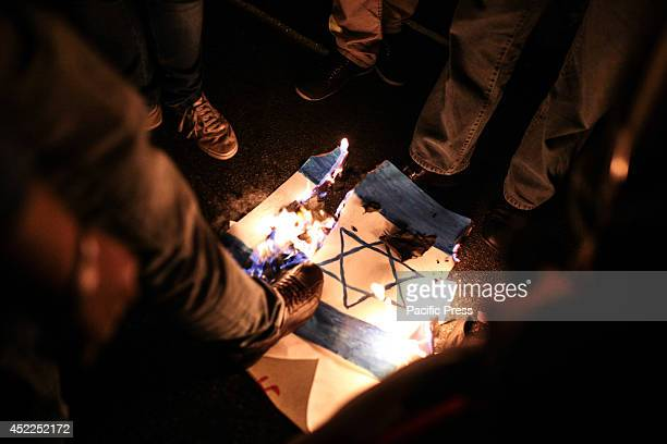 The supporters of the Palestinian cause step on an Israel flag in the middle of a street in Sao Paulo Brazil during a candlelight vigil in support...