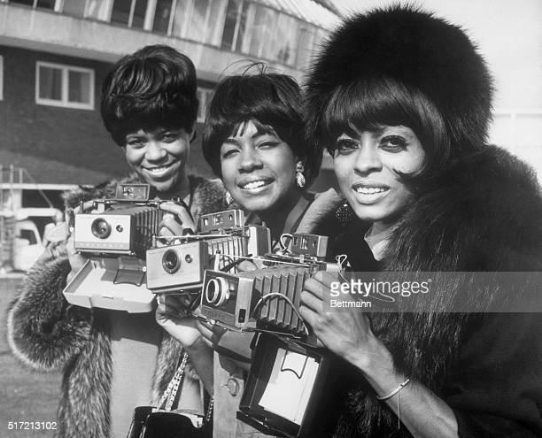 The Supremes pose with their cameras as they arrive at London Airport