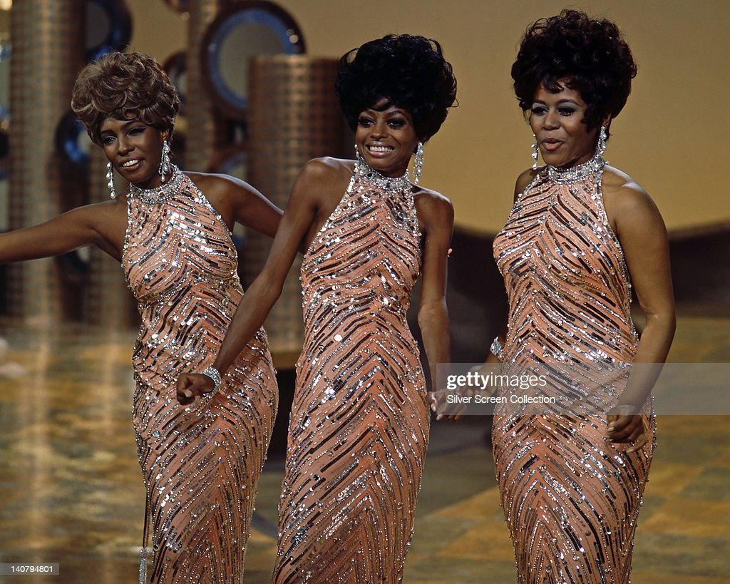 The Supremes wearing matching sequinned peach dresses with silver necklaces and earrings during a live concert performance circa 1965