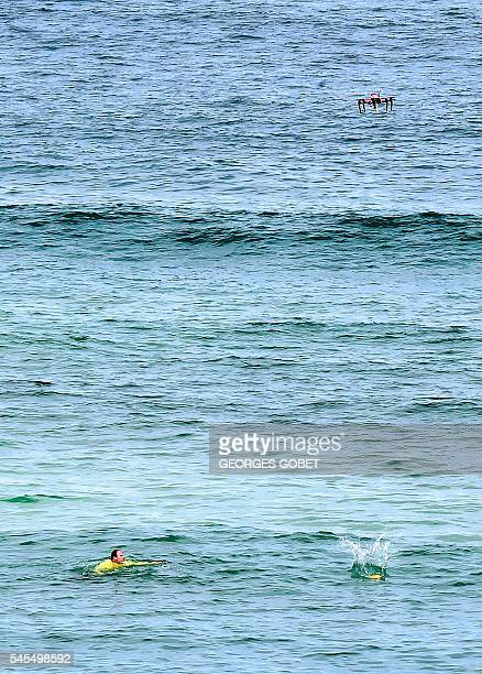 The surveillance drone 'Helper' drops a life buoy to a swimmer in distress next to the beach of Biscarrosse on July 8 during a demonstration of a sea...