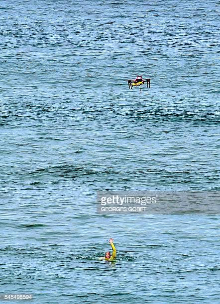 The surveillance drone 'Helper' flies over a swimmer in distress next to the beach of Biscarrosse on July 8 during a demonstration of a sea rescue...