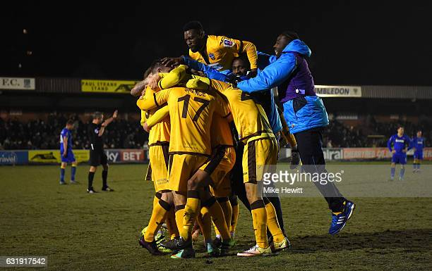 The Sutton United team celebrate victory after the Emirates FA Cup third round replay between AFC Wimbledon and Sutton United at The Cherry Red...