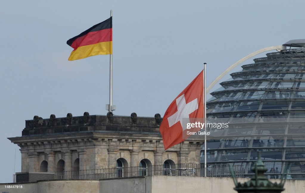 The Swiss flag flies over the Swiss Embassy as the German flag flies over the Reichtsag behind on July 16, 2012 in Berlin, Germany. Authorities in the German state of North Rhine-Westphalia announced recently that they had bought a data CD containing the names of 1,000 German citizens who are using a Switzerland-based bank to evade paying taxes in Germany. The announcement is not the first instance of German tax authorities buying similar CDs, and as a consequence of the incidents Germany and Switzerland have reached an agreement over the assets of German citizens deposited in Swiss banks, though the agreement has not yet become law.