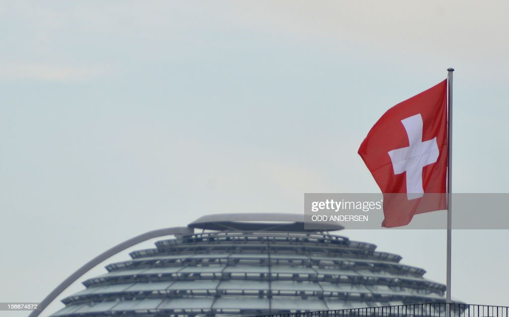 The Swiss flag flutters on the Swiss embassy as in background can be seen the cupola of the Reichstag building housing the lower house of parliament on November 23, 2012 in Berlin. German lawmakers in the upper house of parliament rejected a deal on the taxation of German assets parked in Swiss bank accounts. AFP PHOTO / ODD ANDERSEN