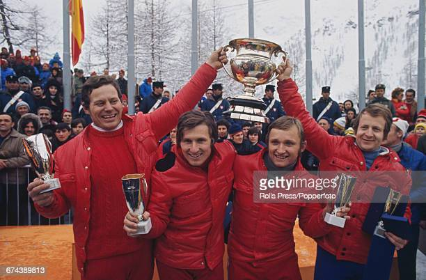 The Swiss four man bobsleigh team of Max Forster Peter Scharer Erich Scharer and Rene Stadler celebrate with the trophy and cups after finishing in...