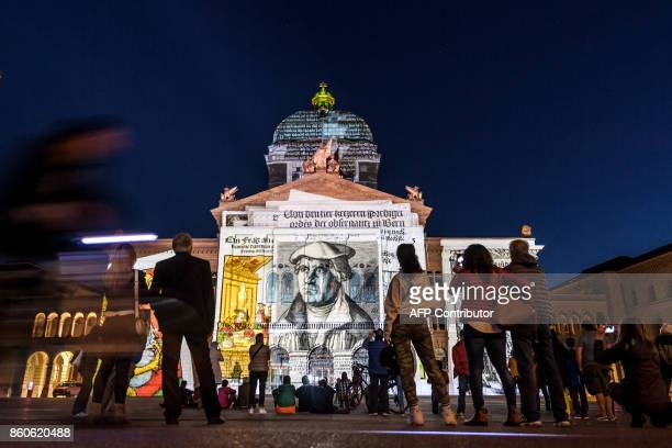 The Swiss House of Parliament is illuminated during a light show entitled 'Rendezvous Bundesplatz' in the Swiss capital Bern on October 12 2017 The...