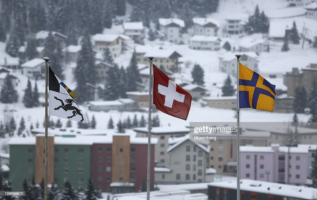 The Swiss national flag, center, flies between flags of the Swiss Canton Graubuenden, or Grisons, in Davos, Switzerland, on Thursday, Jan. 17, 2013. Next week the business elite gather in the Swiss Alps for the 43rd annual meeting of the World Economic Forum in Davos, the five day event runs from Jan. 23-27. Photographer: Chris Ratcliffe/Bloomberg via Getty Images