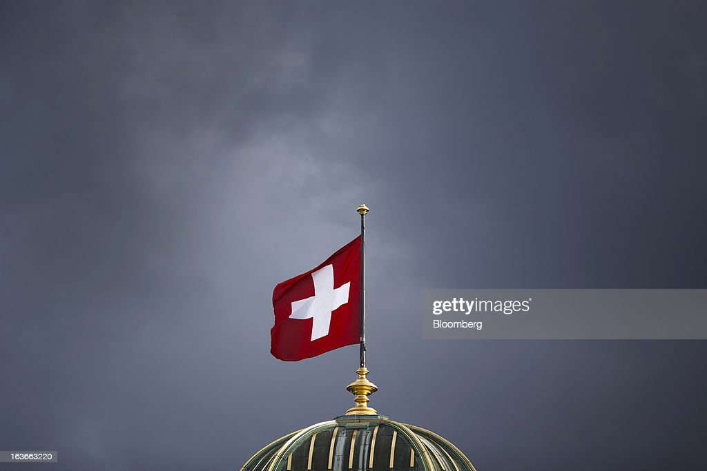 The Swiss national flag flies above the Federal Palace, Switzerland's parliament building in Bern, Switzerland, on Tuesday, March 12, 2013. The Swiss central bank pledged to keep up its defense of the franc cap after almost doubling its currency holdings to shield the country from the fallout caused by the euro zone's crisis. Photographer: Valentin Flauraud/Bloomberg via Getty Images