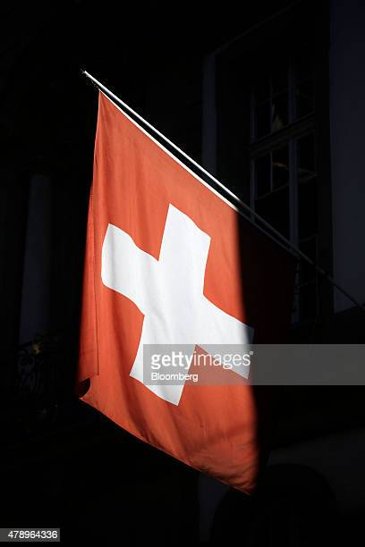 The Swiss national flag is illuminated by evening sunlight as it hangs from a building in Bern Switzerland on Sunday June 28 2015 Swiss National Bank...