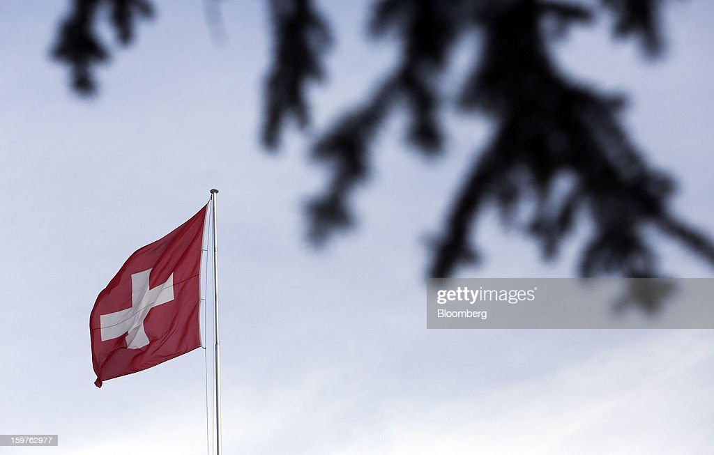 The Swiss national flag is seen flying from a flagpole at a hotel in the town of Davos, Switzerland, on Saturday, Jan. 19, 2013. Next week the business elite gather in the Swiss Alps for the 43rd annual meeting of the World Economic Forum in Davos, the five day event runs from Jan. 23-27. Photographer: Chris Ratcliffe/Bloomberg via Getty Images