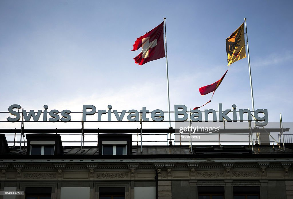 The Swiss national flag, left, flies alongside the Geneva Canton flag, right, on top of the Bank Hapoalim (Switzerland) Ltd. (BHI) offices in Geneva, Switzerland, on Monday, Oct. 29, 2012. Geneva's banks employed 502 fewer people at the end of June compared with a year earlier as foreign wealth managers cut jobs and shifted employees to other locations, a survey by the city's financial lobby group shows. Photographer: Valentin Flauraud/Bloomberg via Getty Images