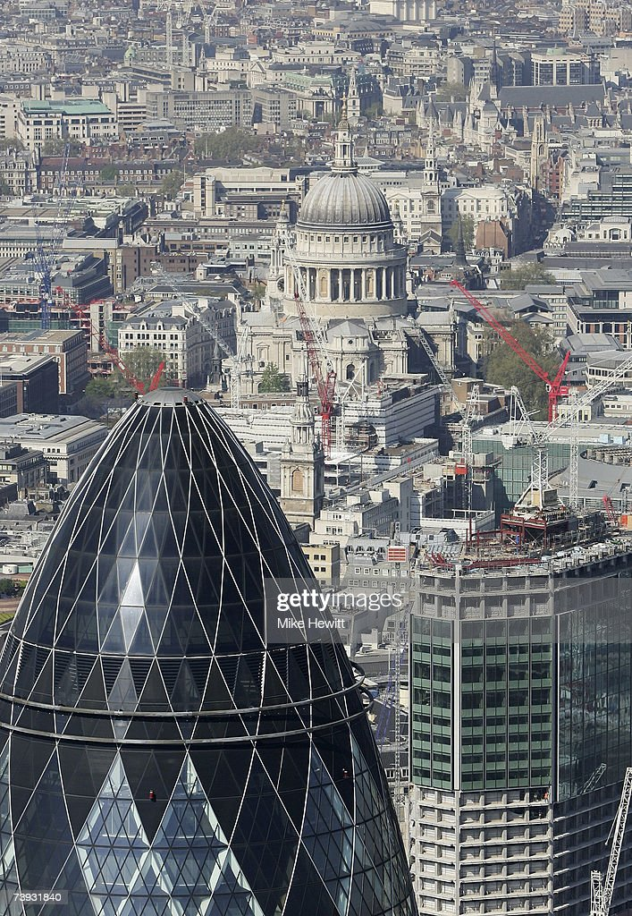 The Swiss Re 'Gherkin' building in front of St Paul's Cathedral on April 20, 2007 in the city of London, England.