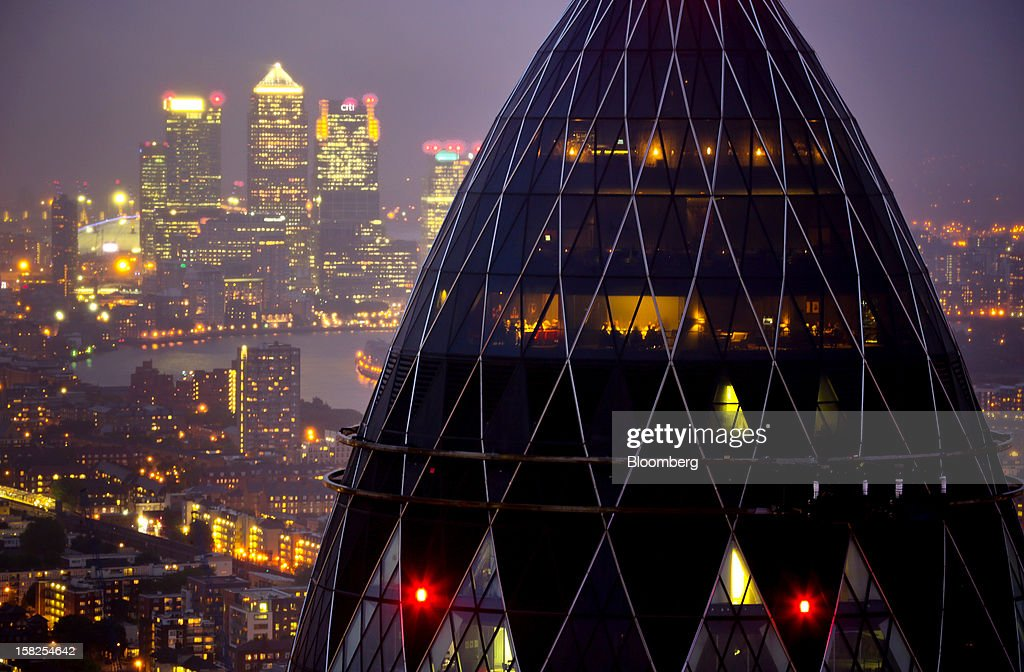 'BEST PHOTOS OF 2012' (): The Swiss Re Insurance building, also known as 'the Gherkin', foreground, and the towers of the Canary Wharf business district are seen against the city skyline in London, U.K. on Thursday, July 12, 2012. Banks being probed for attempting to rig benchmark interest rates could face $6 billion of related litigation costs, analysts at Morgan Stanley estimated. Photographer: Jason Alden/Bloomberg via Getty Images