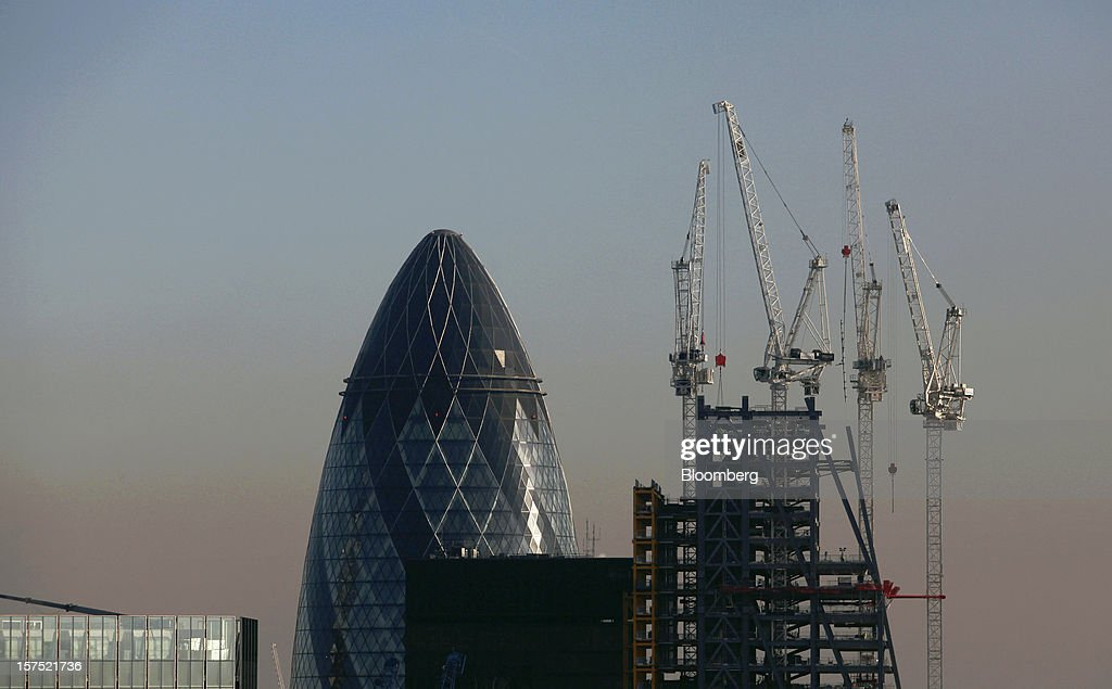 The Swiss Re Insurance building, also known as 'the Gherkin', left, stands beyond the construction site for the Leadenhall building, right, in London, U.K., on Friday, Nov. 30, 2012. U.K. banks have become more unwilling to finance development projects without a tenant committed to lease space or a buyer for the completed property. Photographer: Chris Ratcliffe/Bloomberg via Getty Images