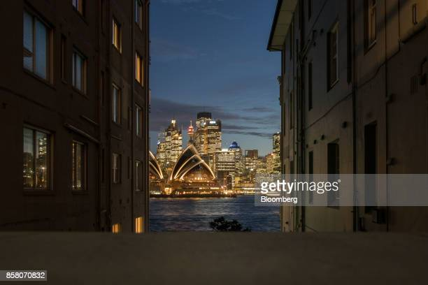 The Sydney Opera House center left and buildings in the financial district are seen between residential blocks as they stand illuminated at dusk in...