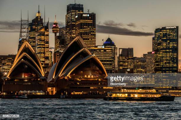 The Sydney Opera House foreground and buildings in the financial district stand illuminated at dusk in Sydney Australia on Friday Sept 29 2017 A...