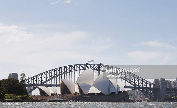 The Sydney Opera House is seen in front of the Sydney Harbour Bridge where the Australian and New South Wales flags are at half mast as a mark of...