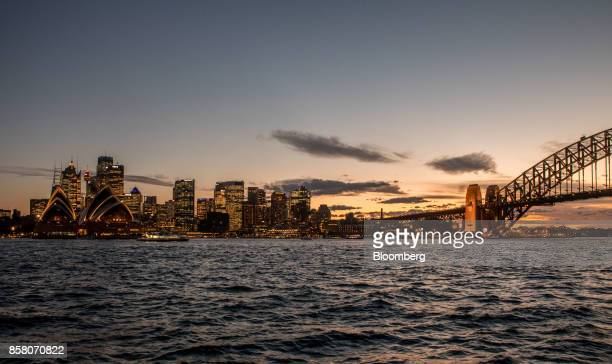 The Sydney Opera House left and buildings in the financial district stand illuminated at dusk in Sydney Australia on Friday Sept 29 2017 A bungled...