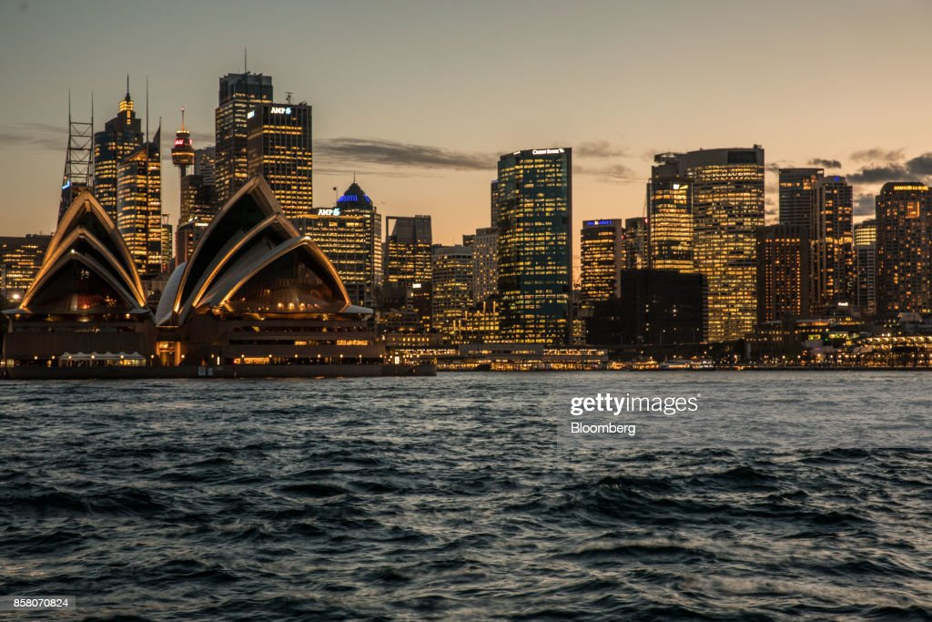 The Sydney Opera House, left, and buildings in the financial district stand illuminated at dusk in Sydney, Australia, on Friday, Sept. 29, 2017. A bungled transition from coal to clean energy has left resource-rich Australia with an unwanted crown: the highest power prices in the world. Photographer: Cole Bennetts/Bloomberg via Getty Images
