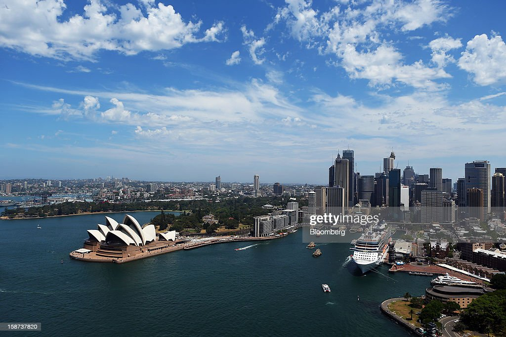 The Sydney Opera House, left, and the Overseas Passenger Terminal at Circular Quay, right, are viewed from the arch of the Sydney Harbour Bridge in Sydney, Australia, on Monday, Dec. 24, 2012. Beginning next month, people wanting to ascend 134 meters above sea level to the top of the bridge spanning Sydney Harbour will have the option to hear guides speak Mandarin. Photographer: Brendon Thorne/Bloomberg via Getty Images