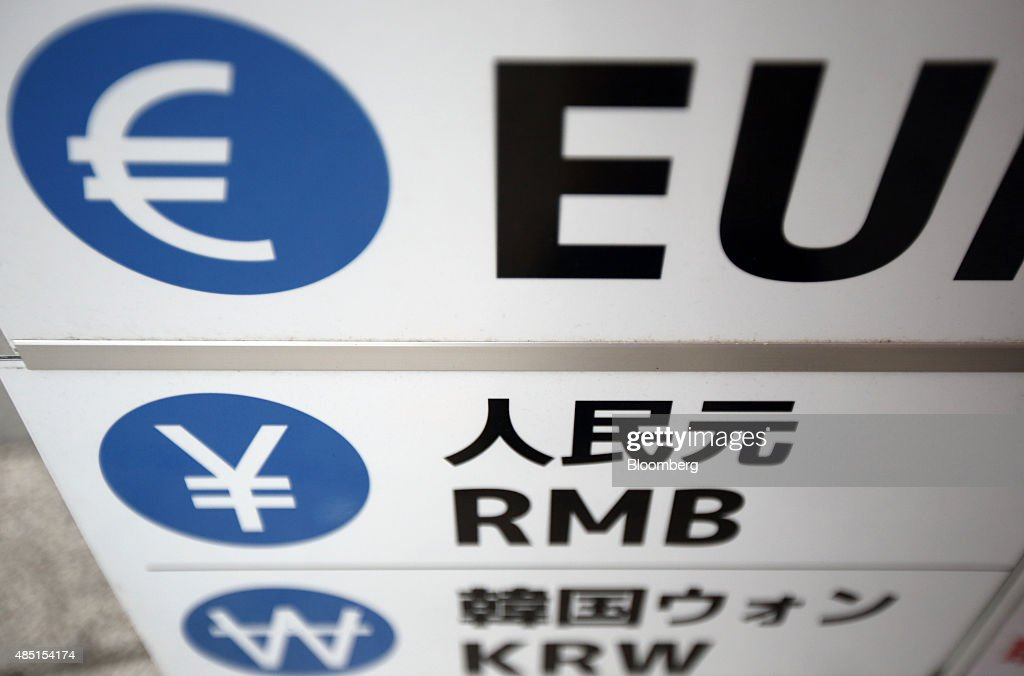 The symbols for the euro top Chinese yuan center and South Korean won are displayed outside a currency exchange store in Tokyo Japan on Tuesday Aug...