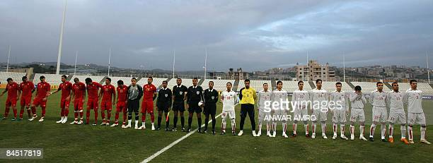 The Syrian and the Lebanese national football teams line up with the match officials before kickoff of their group D 2011 Asian Cup qualifying...
