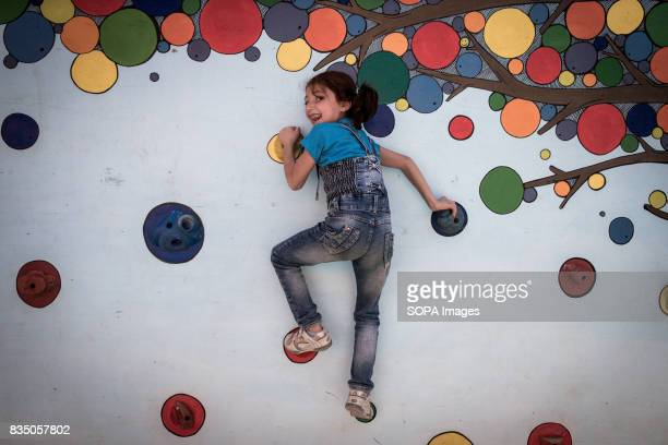 The Syrian daughter of one of the teachers at the school in Al Marj climbs the purpose built climbing wall at the school for children to play on