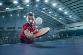 The table tennis player in motion. Fit young sports man tennis-player in play on sport arena background with lights. Movement, sport game, stobe concepts. Professional. Human emotions, facial expressi