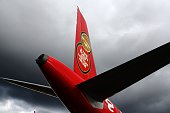 The tail fin of an Air Asia Airbus A320 is seen beside the runway during the Farnborough Airshow south west of London on July 12 2016 German airline...