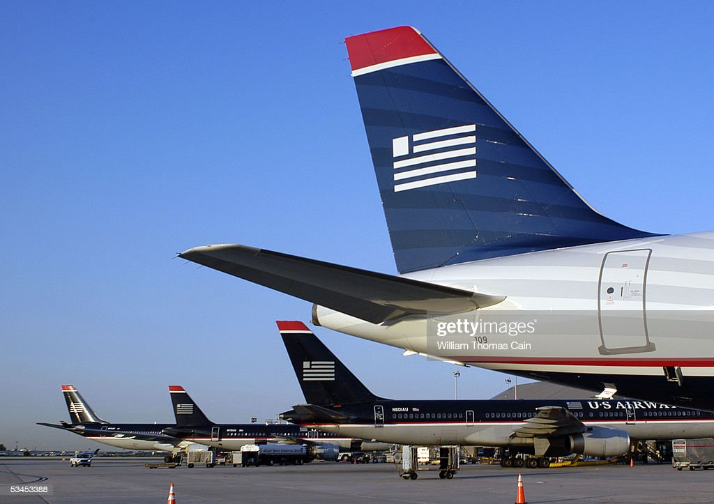 The tail of a new US Airways airplane rests in front of some of the older models during a news conference unveiling America West US Airways new...