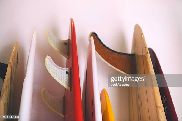 The tails of a series of surfboards rests against the wall in a surfboard shop, Hawaii.