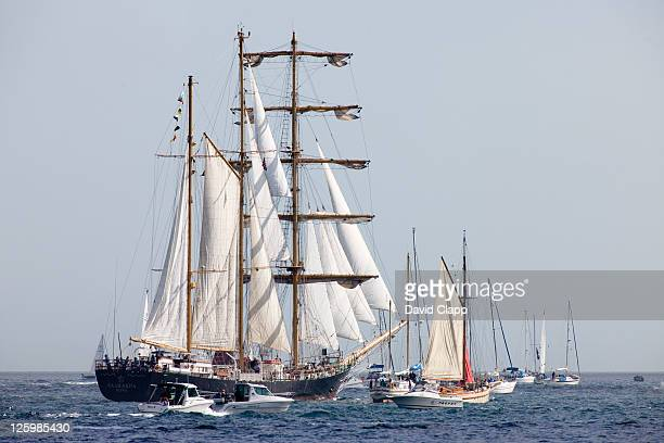 The tall ship Kaliakra surrounded by a flotilla of local boats and yachts. It was built at the Gdansk Shipyard, Poland in 1984 and is owned by Navigation Maritime Bulgare, Falmouth, Cornwall, England