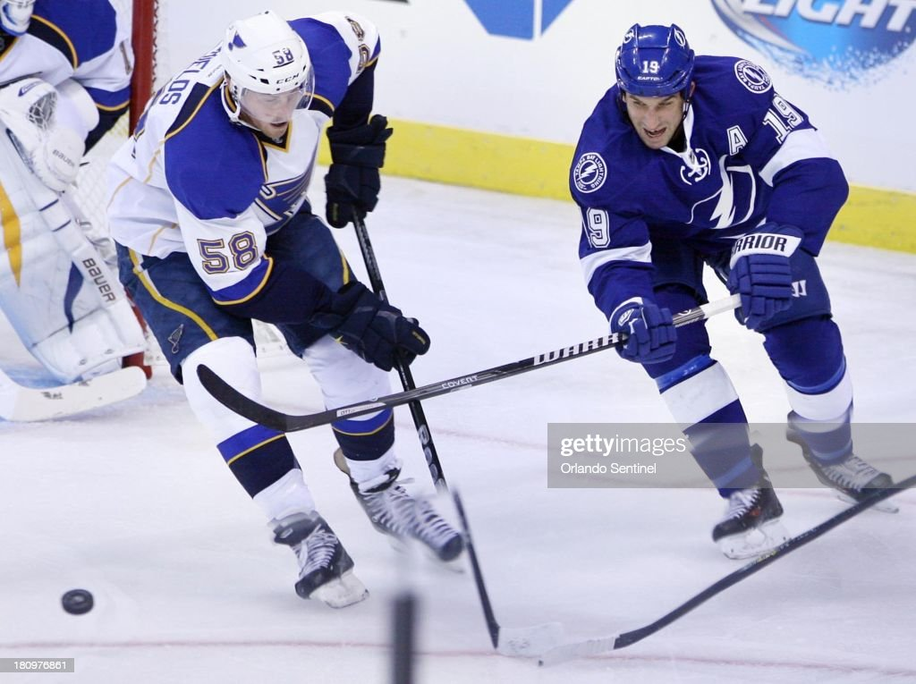 The Tampa Bay Lightning's B.J. Crombeen (19) and the St. Louis Blues' David Shields (58) chase the puck at the Amway Center in Orlando, Florida, on Wednesday, September 18, 2013.