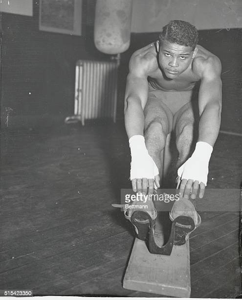The tapering off period of his training grind has come for Joe Louis and the Detroit heavyweight is seen here giving his muscles a mild workout on...