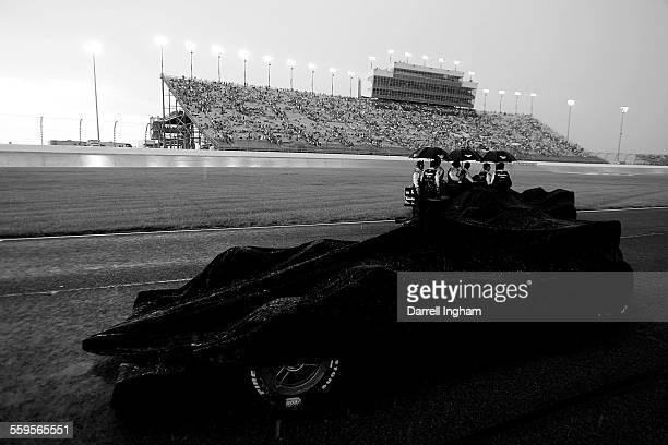 The Target Chip Ganassi Racing Dallara Honda of Scott Dixon is covered up as the crew members for the Andretti Green Dallara Honda of Dario...
