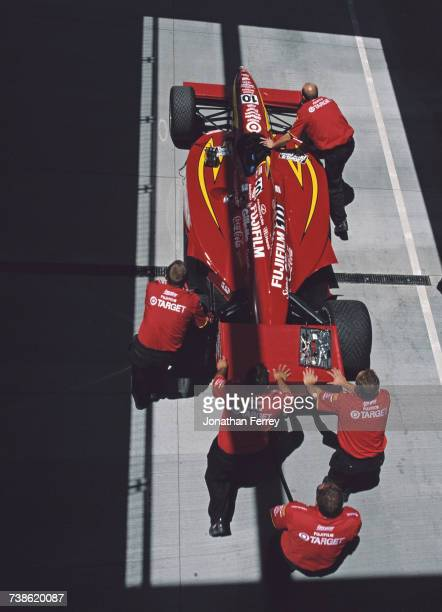 The Target Chip Ganassi Racing GForce GF05a Oldsmobile of Jimmy Vasser is pushed through Gasoline Alley by team mechanics during practice for the...