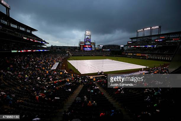 The tarp covers the field during a weather delay before an Interleague game between the Los Angeles Angels of Anaheim and Colorado Rockies at Coors...
