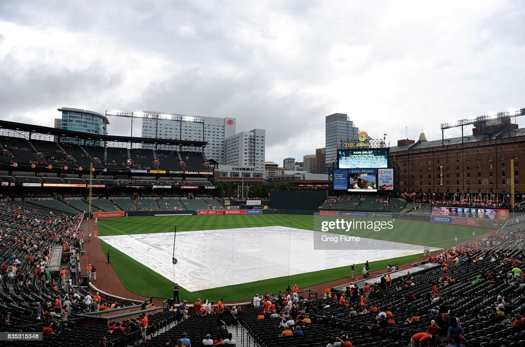 The tarp is on the field before the game between the Baltimore Orioles and the Los Angeles Angels at Oriole Park at Camden Yards on August 18, 2017 in Baltimore, Maryland. The start of the game has been delayed for weather.