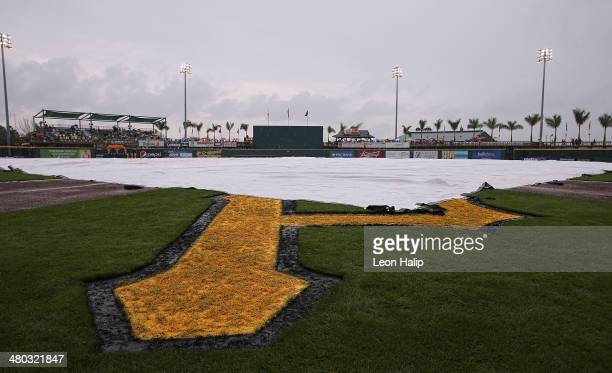 The tarp lies on the field as baseball game between the Detroit Tigers and the Pittsburgh Pirates remains delayed due to rain at McKechnie Field on...